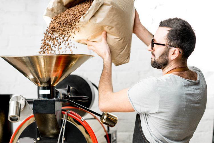 A man pouring a large bag of coffee beans into a coffee roasting machine